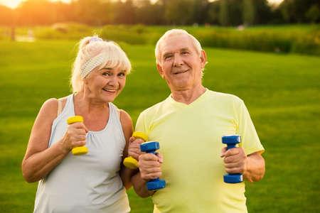 Paar met halters lacht. Oude man en vrouw buitenshuis. Alle doelen haalbaar zijn. Blijf gezond en gemotiveerd.