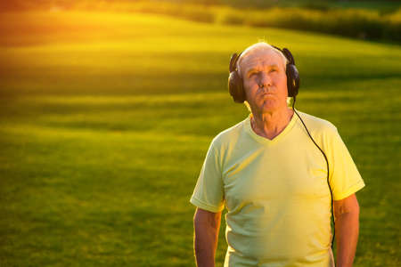 ballad: Elderly man in headphones. Person with serious face outdoor. Good music doesnt get old. Best rock ballads.