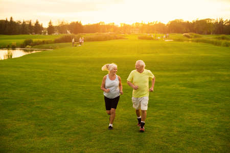 Elderly couple is jogging. Smiling people on meadow. Be in motion. The lightness of moves.