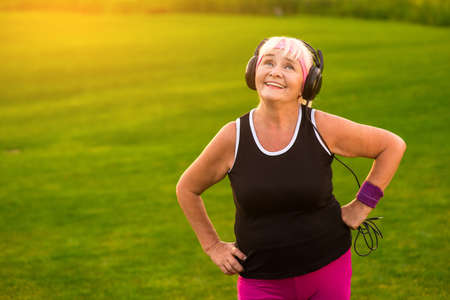 Elderly woman in headphones. Lady smiling and looking up. Music and mood. Tune of my life.