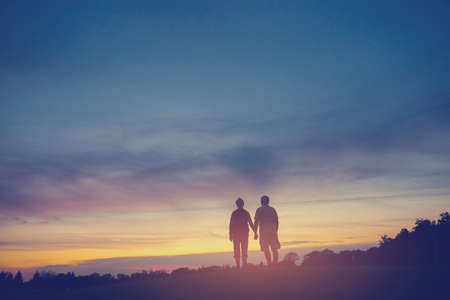 uncover: Couple on background of sunset. Woman and man holding hands. You have my heart. Uncover the secrets of life. Stock Photo