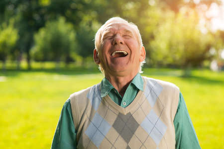 laughing face: Elderly man laughing. Senior male on nature background. Wonderful mood every day. Cant restrain the laughter. Stock Photo