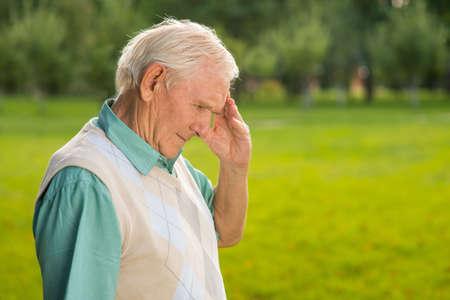 Senior man raakt zijn voorhoofd. Zijaanzicht van de oudere man. Je kunt het verleden niet herschrijven. Moe van alles. Stockfoto