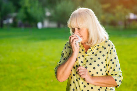 hankie: Senior woman is crying. Lady wiping nose with napkin. No more tears. Grief and despair. Stock Photo