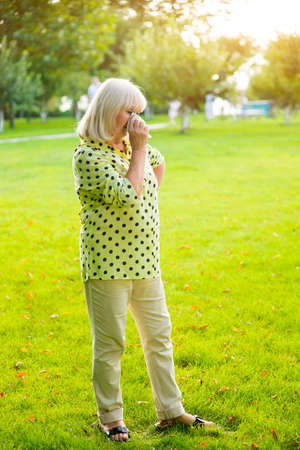 difficult period: Lady wiping eye with handkerchief. Elderly woman standing on grass. Get through a difficult period. Dont lose your dignity.