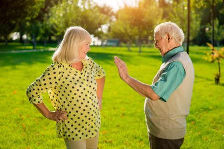 problemas familiares: El hombre y la mujer de pie al aire libre. El varón mayor con la palma levantada. Resolver los problemas de la familia juntos. Dame cinco. Foto de archivo