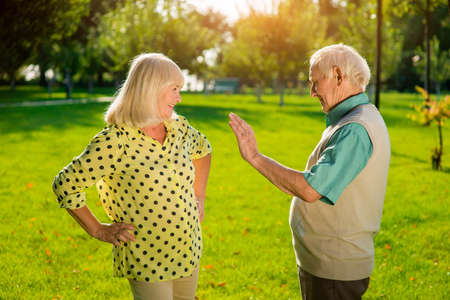 Man and woman standing outdoors. Senior male with raised palm. Solve family problems together. Give me five.