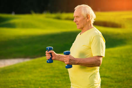 staying fit: Elderly man with dumbbells. Male doing exercise outdoor. Healthy joints and muscles. Always stay in shape.