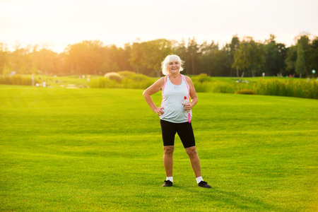 energy needs: Senior woman with water bottle. Lady is standing on grass. Aerobic workouts improve health. All you need is motivation. Stock Photo