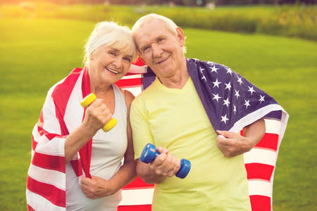 staying fit: Couple of seniors with dumbbells. People with USA flag. Stay true to family values. Health and patriotism.