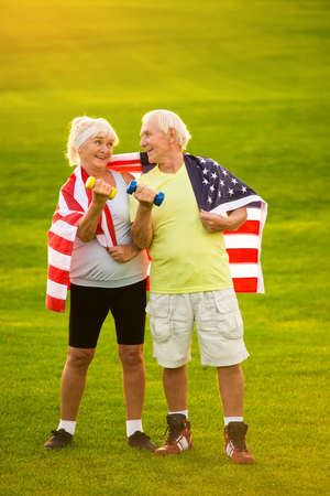 fond: Smiling senior couple with dumbbells. People with USA flag outdoors. Victories of strong nation. Citizens fond of sports.