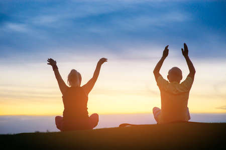 strive: Couple doing yoga. People on sunset sky background. Strive to harmony. Way to peace and balance. Stock Photo
