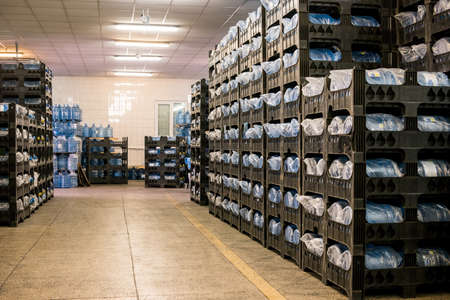 Many water bottles. Rows of crates at storehouse. Good quality guarantees profit. Merchandise supplied to shops.