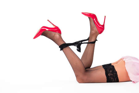 Legs of woman lying. Black panties and red heels. Power of temptation. Eroticism and beauty.
