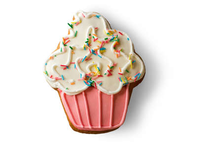 an icing: Cookie shaped as cupcake. Biscuit on white background. Taste of joy. Dough and glaze. Stock Photo