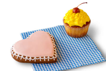 Heart biscuit and yellow cupcake. Pastry on checkered napkin. Surprise for those you love. Find an occasion for holiday. Stock Photo