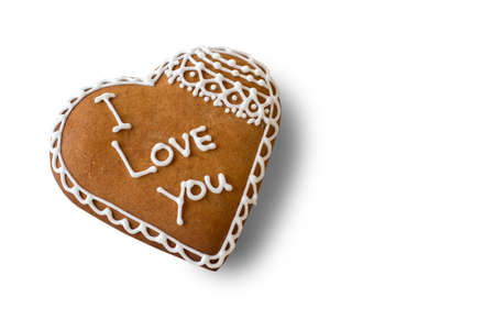 Brown heart shaped cookie. Biscuit with inscription. The most important words. Little present for beloved one. Stock Photo