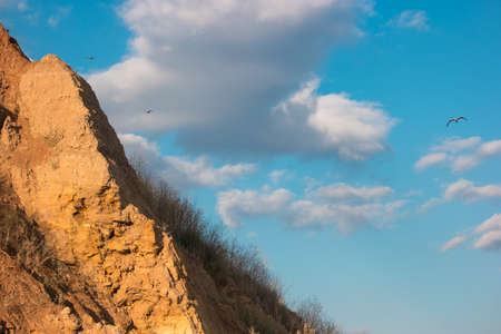long way: Birds flying near a mountain. Cloudy sky and rock. Sense the freedom. Long way to the goal.