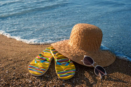 Wicker hat and flip flops. Sand and sunglasses. Get ready for summer. Breathe the sea air. Stock Photo