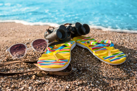 new horizons: Binoculars and flip flops. Sunglasses on sand near water. Time to explore new horizons. Get ready for summer adventures. Stock Photo