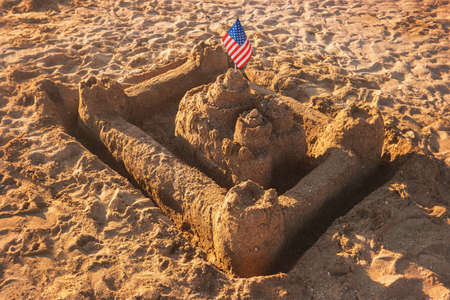strongest: Sandcastle with USA flag. Sand and flag of America. Kingdom of the proud. The strongest fortress. Stock Photo