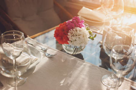 Flowers on dining table. Empty wineglasses and plate. Invite your neighbours for breakfast. Create the absolute cleanliness.