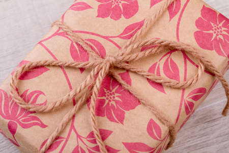 motouz: Flower print wrap and rope. Package on wooden background. Ideas of wrapping gifts. Be thankful for presents.