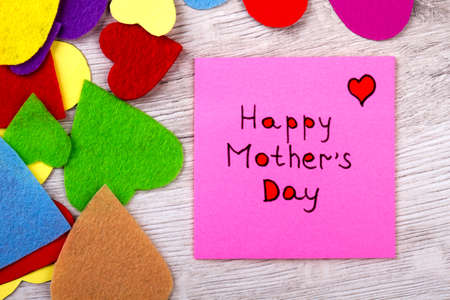 Happy Mother`s Day note. Greeting paper and colorful hearts. Mother deserves pure love. Celebrate your holidays brightly. Stock Photo