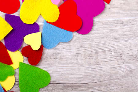 Pile of colorful hearts. Multicoloured hearts on wooden backdrop. Bright holiday congratulation. Decorate table on holiday.