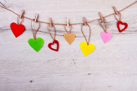 Hearts and clothespins on rope. Multicolor hearts on wooden background. Decorate room on holiday. Always stay positive. Stock Photo