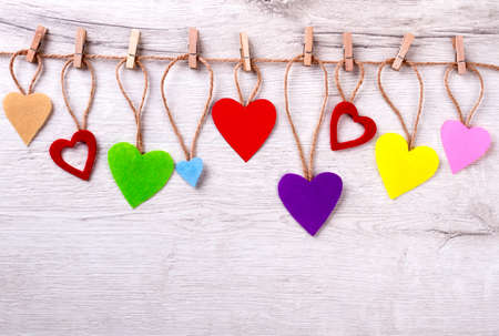 Many colorful hearts on rope. Clothespegs on twine. Add color to your life. Bright suggestion for interior.