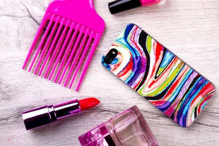 Smartphone en make-up. Parfum, lippenstift en kam. Telefoon als modern accessoire. Maak je op voor een feestje. Stockfoto