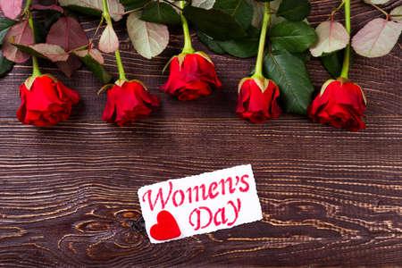 curare teneramente: Fiori con carta Women`s Day. Rose rosse e fondo in legno. Custodire la vostra dolce metà. regalo romantico in vacanza. Archivio Fotografico