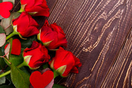 Roses and hearts on wood. Fresh flowers of red color. Impress your beloved girl. Holiday of love and joy.