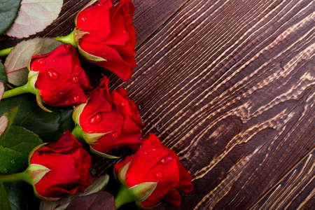 Roses in water drops. Wet flowers on wood. Freshness of holiday morning. Delight of making a present.