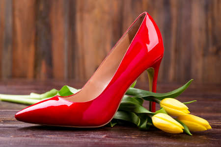 Yellow tulips and heel shoe. Flowers near footwear on wood. Be prepared on holiday. Well-aimed idea of a gift. Zdjęcie Seryjne