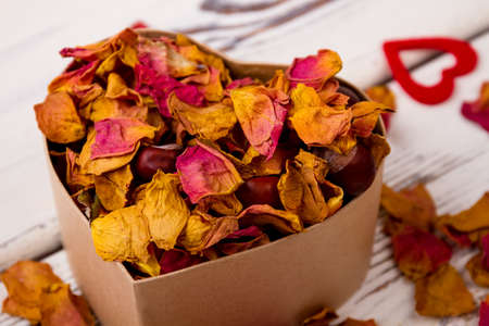passion fruit flower: Potpourri and chestnuts in box. Heart near box with potpourri. Aroma of romance. Stock Photo