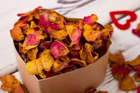 potpourri: Potpourri and chestnuts in box. Heart near box with potpourri. Aroma of romance. Stock Photo