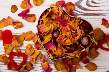 potpourri: Heart-shaped box with rose potpourri. Chestnuts, dried petals and hearts. Design on day of love. Stock Photo