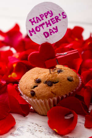 Mother`s Day card and muffin. Heart, cupcake, card and petals. Delicious present for mommy.