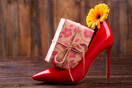curare teneramente: Present box near shoe. Flower, gift and footwear. Cherish your lady. Many presents better than one. Archivio Fotografico
