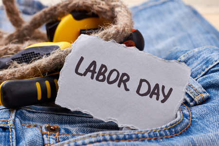 Labor Day card near rope. Tools and paper on jeans. Relax on holiday.