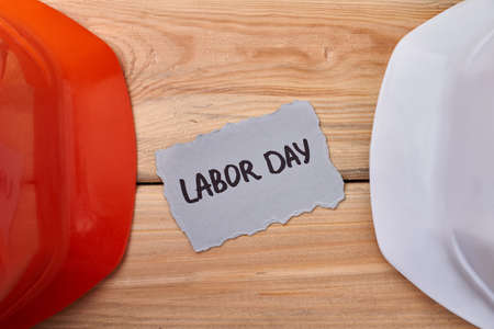 hard hats: Helmets and Labor Day card. Hard hats on wooden background. Safety is always a priority.