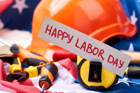 Helmet near Labor Day card. American flag and tools. Success starts with hard work.