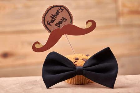 Muffin con baffi. Cartolina d'auguri e cravatta di arco. Delizioso regalo per papà. Archivio Fotografico - 67746489