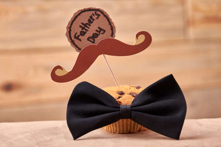 Muffin with mustache. Greeting card and bow tie. Delicious gift for daddy. Reklamní fotografie - 67746489