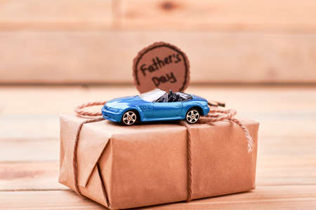 Greeting card and toy car. Present box on light background. Drive responsibly on holiday.