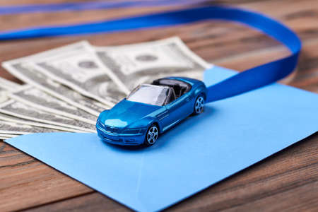 path to wealth: Envelope with dollars and ribbon. Blue envelope near plastic car. Long hard path to wealth.