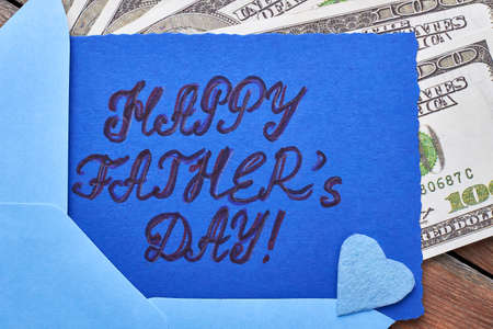 Dollars near Fathers Day card. Blue fabric heart on card. Financial support for dad.