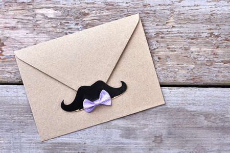 props: Bow tie on envelope. Props mustache near bow tie. Stylish party invitation. Stock Photo
